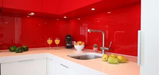 Белая столешница, контрастирующая с интенсивным красным цветом подвесных шкафов и стекла на стене, освещают противотуманки, установленные в нижней части шкафов