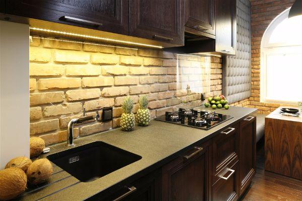 Панель с лампами- установленными на нижней части шкафов освещает столешницу. Теплый желтый цвет освещения идеально подходит для кирпича над столешницей