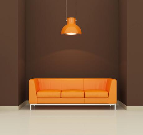 оранжевый диван на фоне темной стены