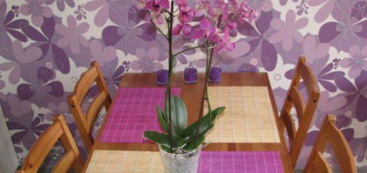 Фиолетовые обои и ткань в цвет фуксии, тонизирует теплое дерево кухонного стола. К этим натуральным цветам отлично подходят зеленые листья фиолетовой орхидеи