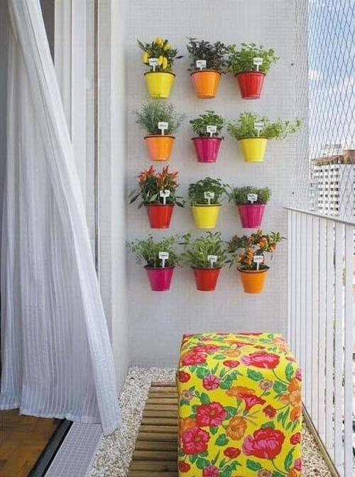 разноцветные горшки на стене балкона