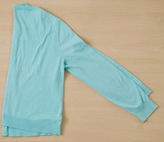 Шаг 1: Сложите свитер пополам с рукавами вместе