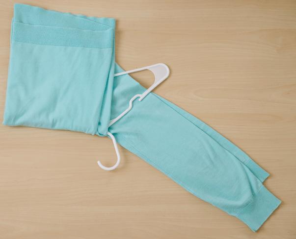 Сложите тело свитера на талии над одной стороной вешалки
